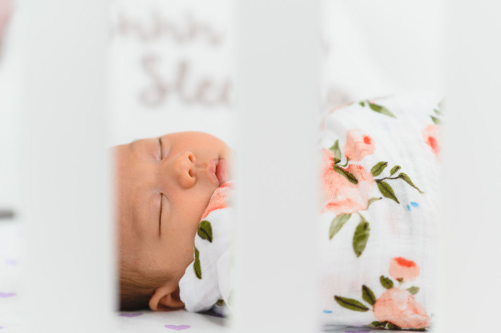 A baby swaddled in a floral blanket Toronto family photography How To Make Your Newborn Photoshoot Go Really Smoothly