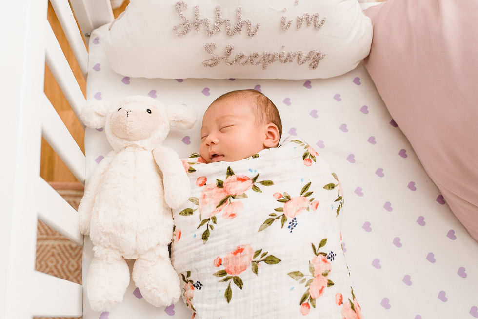 A baby swaddled in a floral blanket and sleeping in a crib with stuffed bunny and a pillow that says shhh i