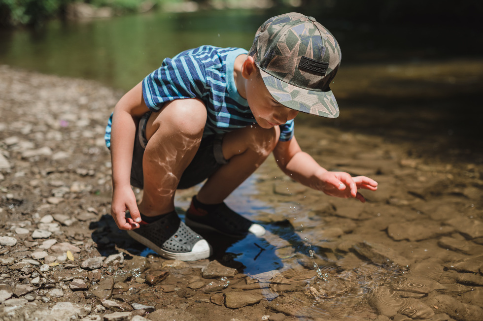 Boy looking into the water throwing a stone